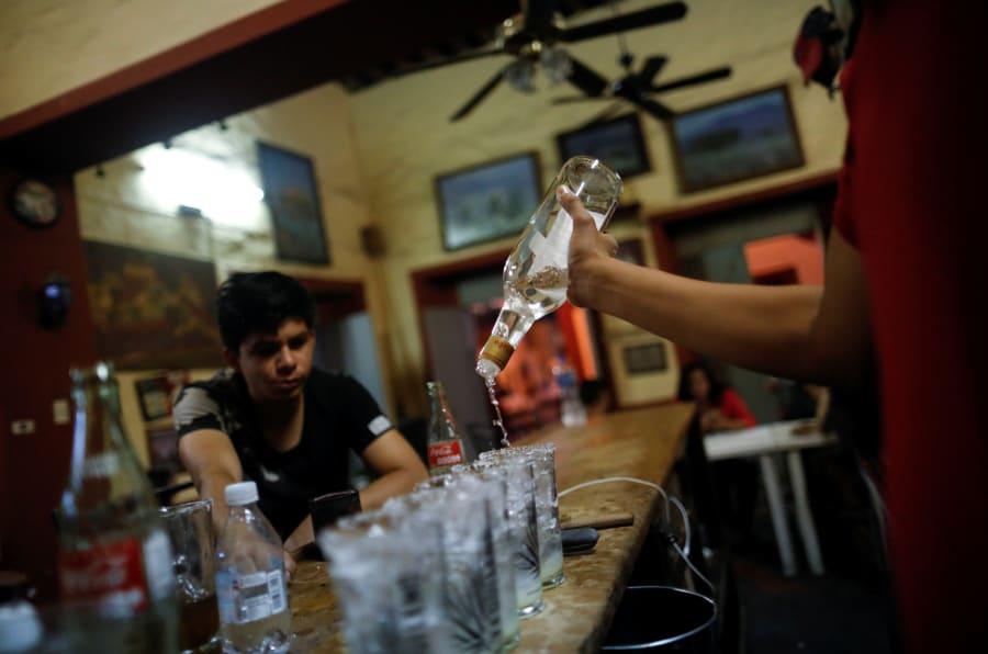 """Un residente observa mientras el camarero vierte tequila en una bebida tradicional llamada """"Batanga"""" en el bar La Capilla en Tequila, Jalisco."""