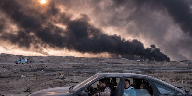 A family flees the fighting in Mosul, Iraq's second-largest city, as oil fields burned in Qayyara, Iraq, on Nov. 12, 2016. This image won second place in the General News stories category.