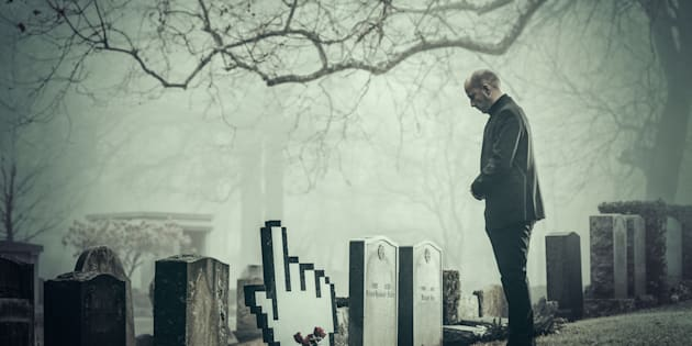 Man in graveyard by gravestone in the shape of a hand cursor