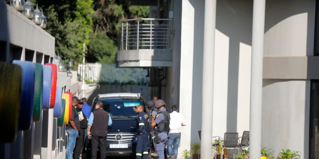 A police van and uniformed and plainclothes police officers are seen inside the Saxonwold property of the Gupta family while cars belonging to the Hawks, the Directorate for Priority Crime Investigation, are stationed outside.