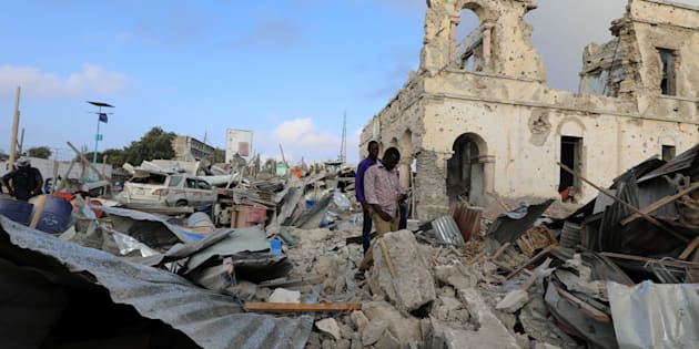 Civilians look at the scene after a suicide car explosion in front of Doorbin hotel in Mogadishu, Somalia February 24, 2018.