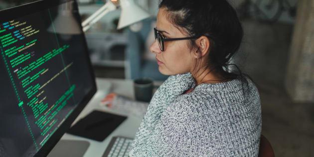 Un mujer trabaja en programación informática en su ordenador.