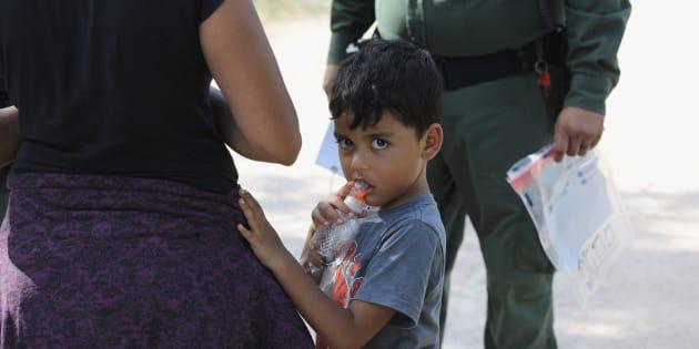 Solicitantes de asilo centroamericanos esperan en la frontera entre México y Estados Unidos a que un agente de la Patrulla Fronteriza se los lleve en custodia en McAllen, Texas.