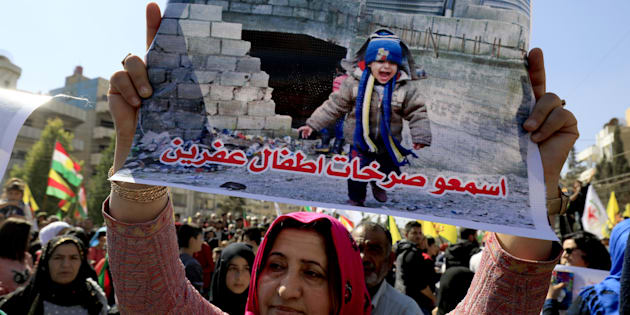 A Syrian Kurdish woman holds a poster during in a protest in the northeastern city of Qamishli, against the Turkish assault on the Syrian border enclave of Afrin, on March 12, 2018. The writing in Arabic reads: 'Hear the screams of Afrin's children'. Two days earlier Ankara-backed rebels advanced against Kurdish militia in northwest Syria, coming to within two kilometres (just over one mile) of the flashpoint town of Afrin, the Syrian Observatory said. / AFP PHOTO / Delil souleiman        (Photo credit should read DELIL SOULEIMAN/AFP/Getty Images)