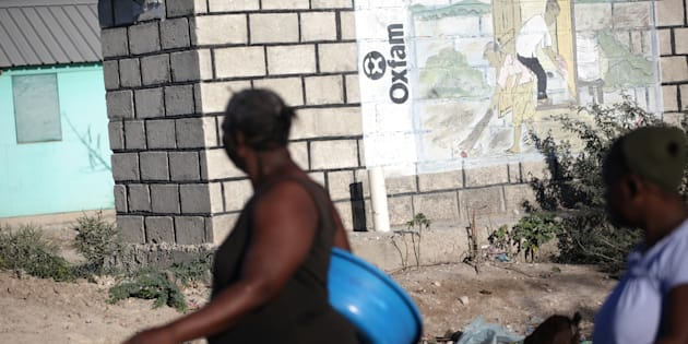 People walk past an Oxfam sign in Corail, a camp for people displaced after 2010 earthquake, on the outskirts of Port-au-Prince, Haiti, February 16, 2018