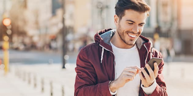 Un joven viendo su teléfono móvil en la ciudad.