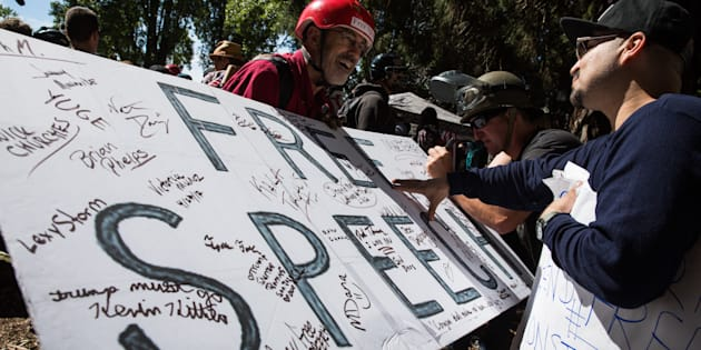 Jeff Barnes (left) of Alameda, Calif., invites people to sign a free speech sign during a pro-Donald Trump rally at Martin Luther King Jr. Civic Center Park in Berkeley, Calif., on April 27, 2017. The co-opting of the free speech mantle by conservatives has some progressives convinced that free speech itself is no longer worth defending.