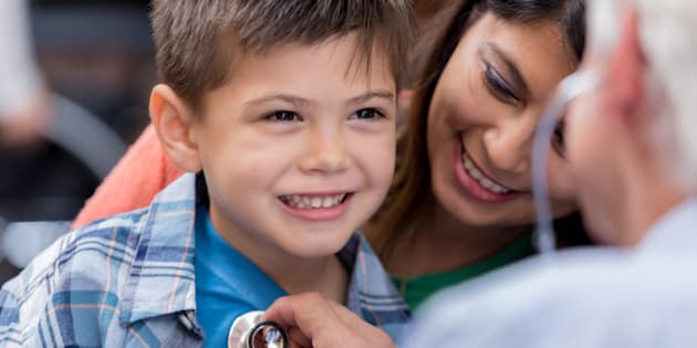 Cute elementary age boy smiles while pediatrician checks his heart and lungs with a stethoscope.