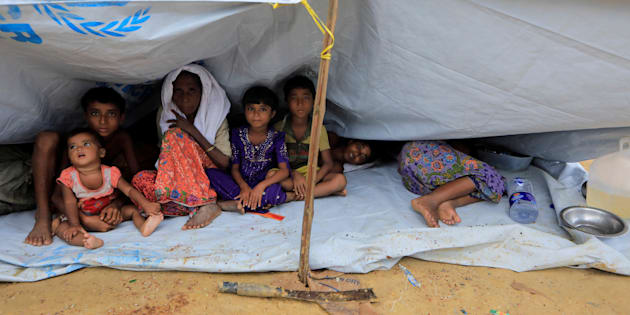 Rohingya refugees who crossed the border from Myanmar this week sit outside a school used as a shelter at Kotupalang refugee camp near Cox's Bazar, Bangladesh October 20, 2017. REUTERS/ Zohra Bensemra