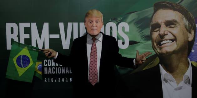 Un hombre posa con una máscara de Trump frente a un cartel del candidato brasileño de ultraderecha, Bolsonaro.