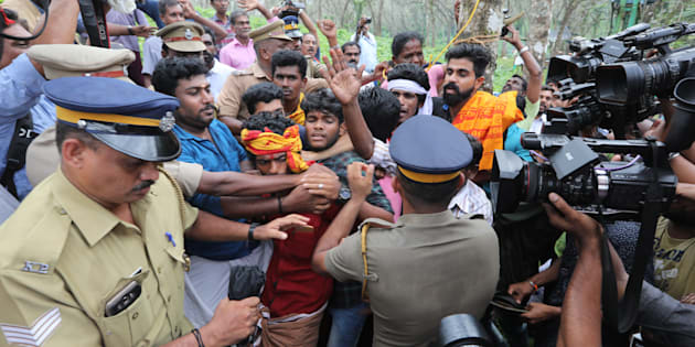 Ratnaamma, a Hindu devotee is surrounded by other devotees as she threatens to commit suicide in protest against the lifting of ban by Supreme Court that allowed entry of women of menstruating age to the Sabarimala temple, at Nilakkal base camp on October 16, 2018 in Pathanamthitta, Kerala.