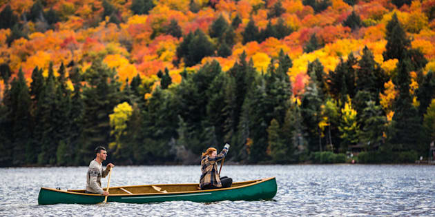 A couple enjoys a ride on a canoe in Algonquin Park in Ontario.