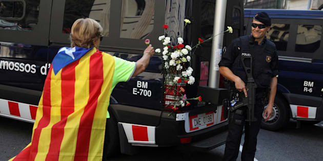 Una mujer con una estelada pone claveles en un vehículo de los Mossos, durante una protesta por el veto a la consulta.
