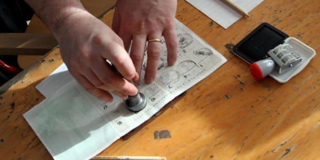 Timbro su una tessera elettorale in una foto d'archivio. ANSA / MATTEO BAZZI