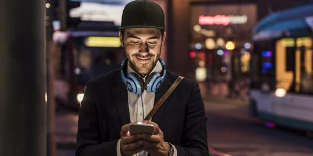 Hombre joven viendo su teléfono celular en la ciudad.