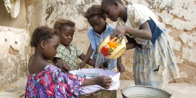 Meninas anteriormente infectadas pelo verme da Guiné filtram a água que vão beber para prevenir a doença.