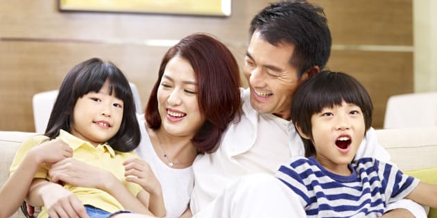 portrait of a happy asian family sitting on couch at home, smiling and laughing.
