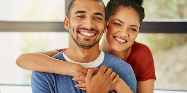 Portrait of a happy young couple embracing at home