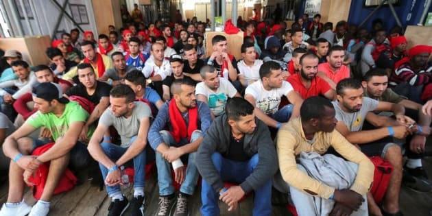 Un grupo de migrantes espera para desembarcar en Crotona (Italia) de un barco de la ONG Save The Children, tras ser rescatados en su periplo desde Libia.