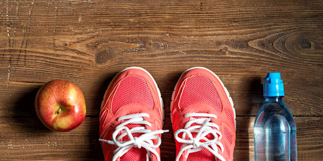 Fitness concept, pink sneakers, red apple and bottle of water on wooden background, top view