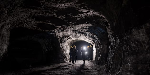 Group of men in a dark mine underground - mining concepts