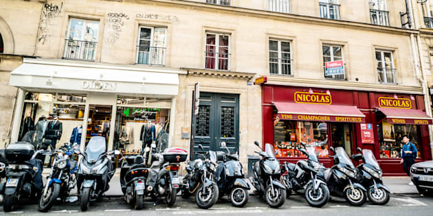 Paris, France - September 26, 2016: Paris street wth shops and motorcycles parked, France. Few people on the street.