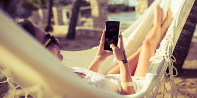 Woman using her phone while relaxing in a hammock by the beach