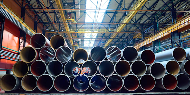 Heap of pipes and tubes of equal size at factory storage prepared for customers