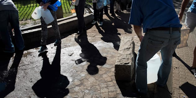 People queue up to collect drinking water from taps fed by a spring in Newlands, Cape Town, in May 2017.