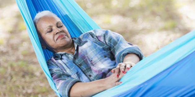 A senior African American woman asleep in a blue hammock.