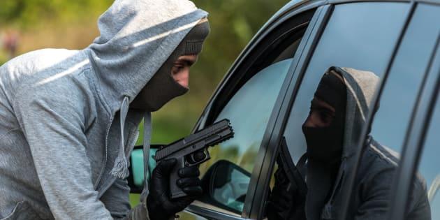 A robber pointing a gun at a driver in a car.