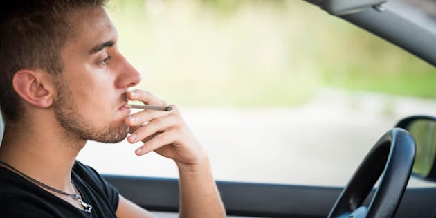 Man driving and smoking joint