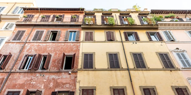 Rome, Italy street in historic center looking up at facade exterior windows wall during sunny summer day, nobody, orange yellow red old colorful painted walls