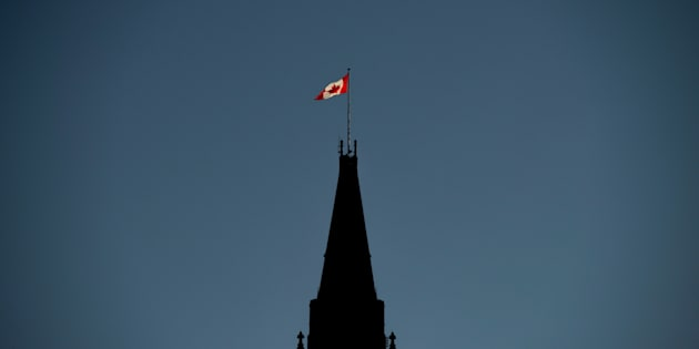 The Canadian Flag is illuminated by morning light atop the Peace Tower on Parliament Hill in Ottawa on Sept. 17, 2018.