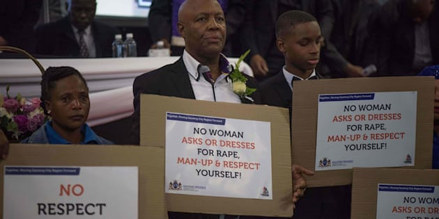 South African men hold placards denouncing violence against women during the memorial service for Karabo Mokoena.
