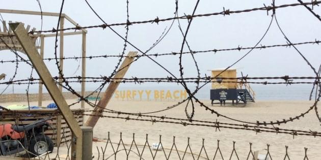 有刺鉄線をくぐった先に広がるサーファーズビーチ「SURFYY BEACH」=5月29日、韓国襄陽郡