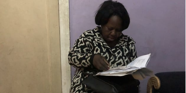 Kundji Tembo goes through her hospital and home affairs documents in a room she is sharing with her daughter and two other family members.