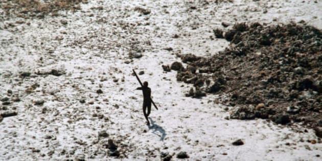 La photo, prise le 28 décembre 2004, montre un homme de la tribu des Sentinelles qui dirige son arc et sa flèche vers un hélicoptère des garde-côtes indiens lors d'un survol de l'île North Sentinel, dans les îles Andaman, en Inde.