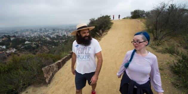 Chuck McCarthy platica con su clienta, Anie Dee, mientras caminan por Hollywood Hills, en un parque en Los Angeles, California.