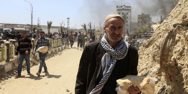 Ciudadanos sirios reciben pan por parte del gobierno en Duma.