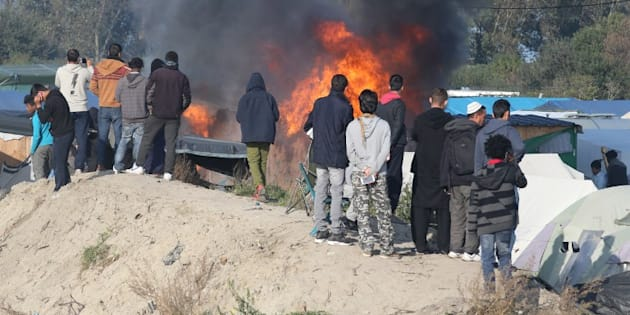 """Des migrants devant des tentes incendiées dans la """"Jungle"""" de Calais le 25 octobre 2016."""