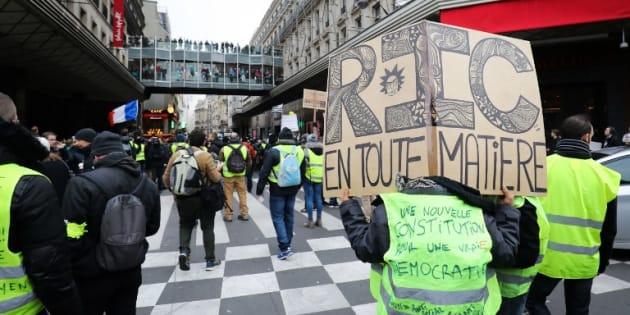"""Un manifestant lors l'acte 9 des gilets jaunes samedi 12 décembre avec une pancarte """"RIC en toute matière""""."""