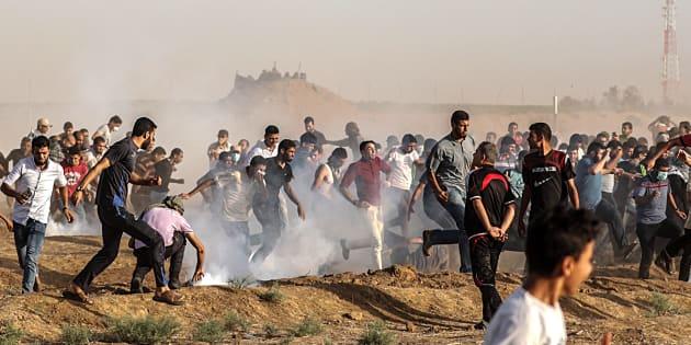 Decenas de palestinos se ponen a cubierto del gas lacrimóeno lanzado por soldados israelíes durante protestas en la frontera de Gaza con Israel, este viernes.