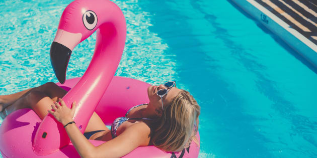 Attractive blonde caucasian woman at the pool, floating on a inflatable pool toy, enjoying time in the summer, vacations in a popular travel destination, taking care of her body
