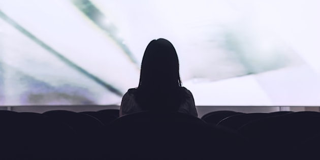 Rear view of woman sitting alone watching movie in empty theatre