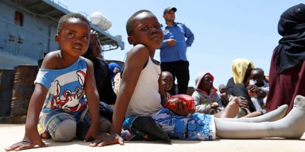Dos niños subsaharianos esperan ayuda en una base naval tras ser rescatados por la guardia costera libia, este viernes.