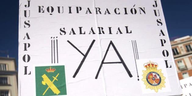 """Un manifestante porta una pancarta en la que se lee: """"Equiparación salarial ya"""", en la protesta celebrada en Madrid en noviembre pasado."""