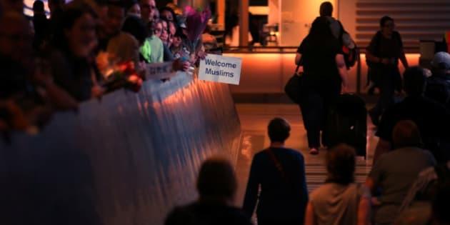 """El ingeniero retirado John Wider sostiene un cartel que dice: """"Welcome Muslims"""" (Bienvenidos, musulmanes), en las llegadas internacionales del aeropuerto de Los Ángeles."""