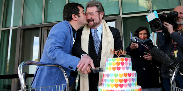 Labor Senator Sam Dastyari gives a kiss to Senator Derryn Hinch over a marriage equality themed cake.
