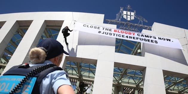 Refugee activists hung a banner from the Great Veranda at Parliament House in Canberra